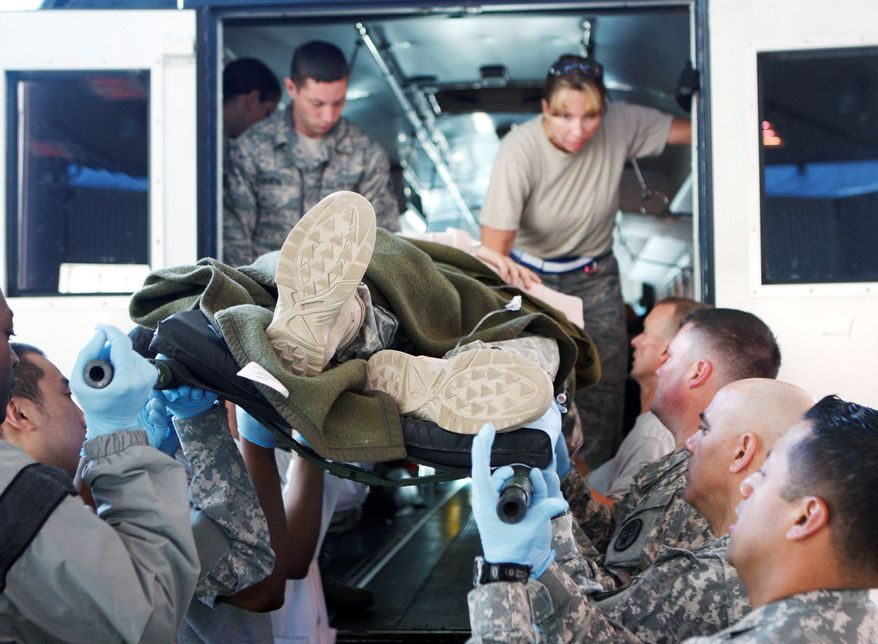 A lot of hands help a wounded U.S. soldier out of a bus in August at Landstuhl Regional Medical Center in Landstuhl, Germany. Landstuhl has treated more than 13,000 combat injuries and some 64,000 noncombat injuries from Afghanistan and Iraq.