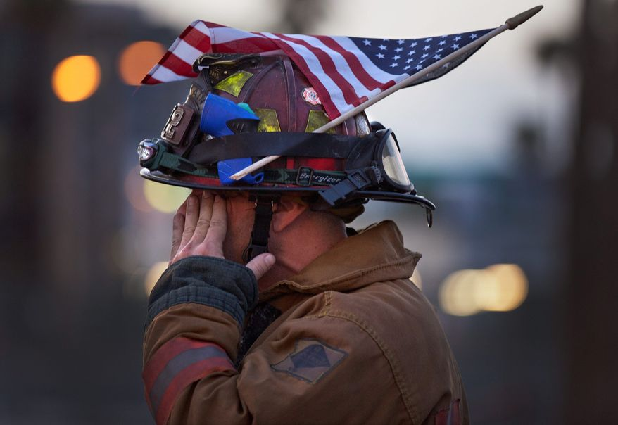 Las Vegas Fire Department Capt. Eric Littmann takes part Sunday in a parade in Las Vegas commemorating lives lost in that act of infamy. (Associated Press)