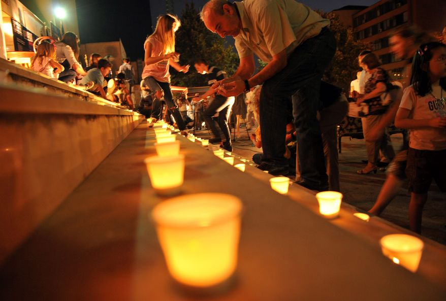 Kosovars light candles in remembrance in the southeast European nation's capital of Pristina, Kosovo, on Sunday. Elsewhere, Kosovar youths sported T-shirts commemorating 9/11 as U.S. peacekeepers secured the area during a military band concert in Urosevac. (Associated Press)