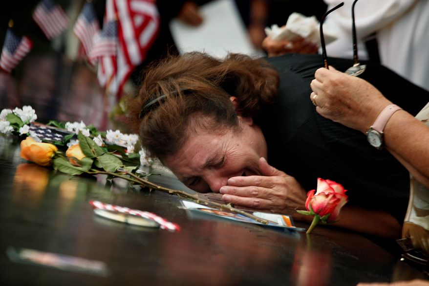A woman at the National September 11 Memorial on Sunday mourns the loss of her son, who died at the World Trade Center 10 years ago Sunday. (Associated Press)