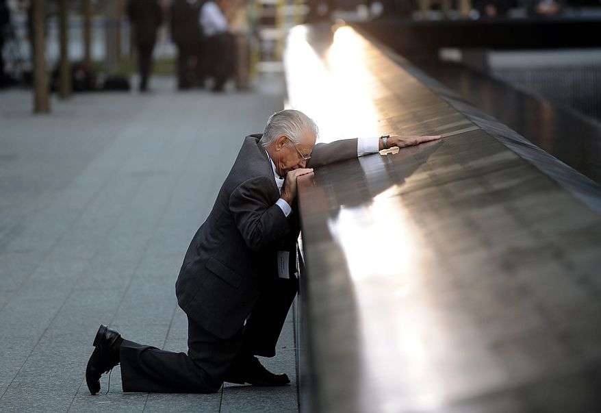 Robert Peraza, who lost his son Robert David Peraza in the attacks at the World Trade Center, pauses at his son's name at the North Pool of the 9/11 Memorial before the 10th anniversary ceremony at the site, Sunday Sept. 11, 2011, in New York. (AP Photo/Justin Lane, Pool)