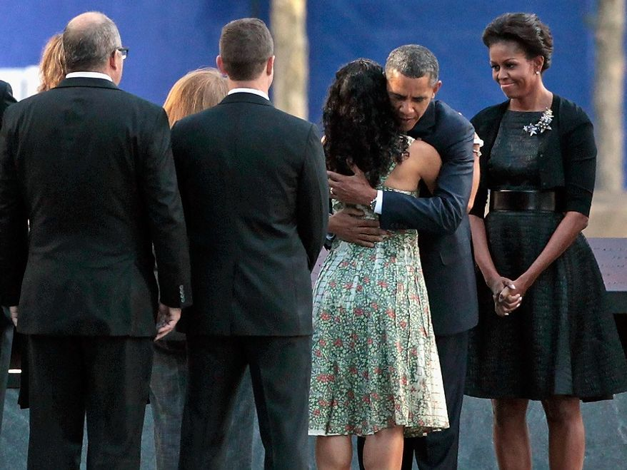 President Obama embraces the family member of a victim of the Sept. 11 terrorist attacks as first lady Michelle Obama (right) looks on during the 10th-anniversary ceremony at the Sept. 11 Memorial at ground zero in New York on Sunday, Sept. 11, 2011. (AP Photo/Chip Somodevilla, Pool)