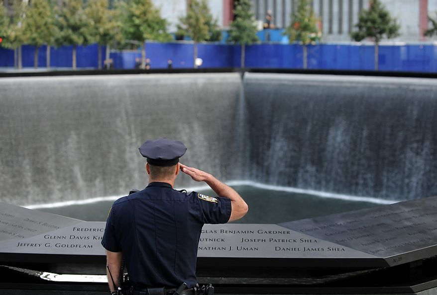 A New York City police officer salutes at the north pool of the Sept. 11 memorial as the national anthem is sung during the 10th anniversary ceremonies at the World Trade Center, Sunday, Sept. 11, 2011, in New York. (AP Photo/Justin Lane, Pool)