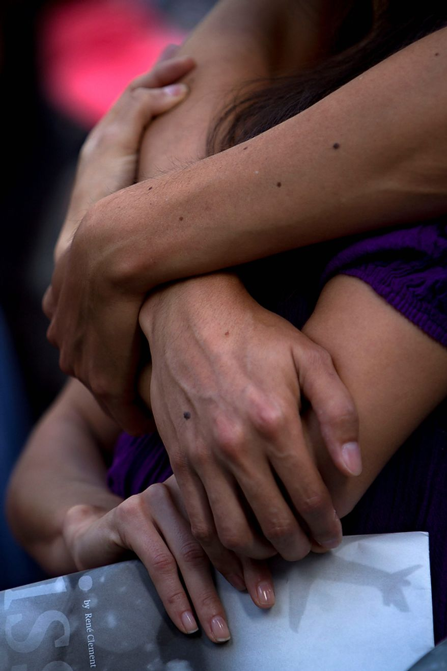 People pay their respect during a ceremony marking the 10th anniversary of the attacks on the World Trade Center Sunday, Sept. 11, 2011, outside the World Trade Center site in New York. (AP Photo/(AP Photo/Oded Balilty)
