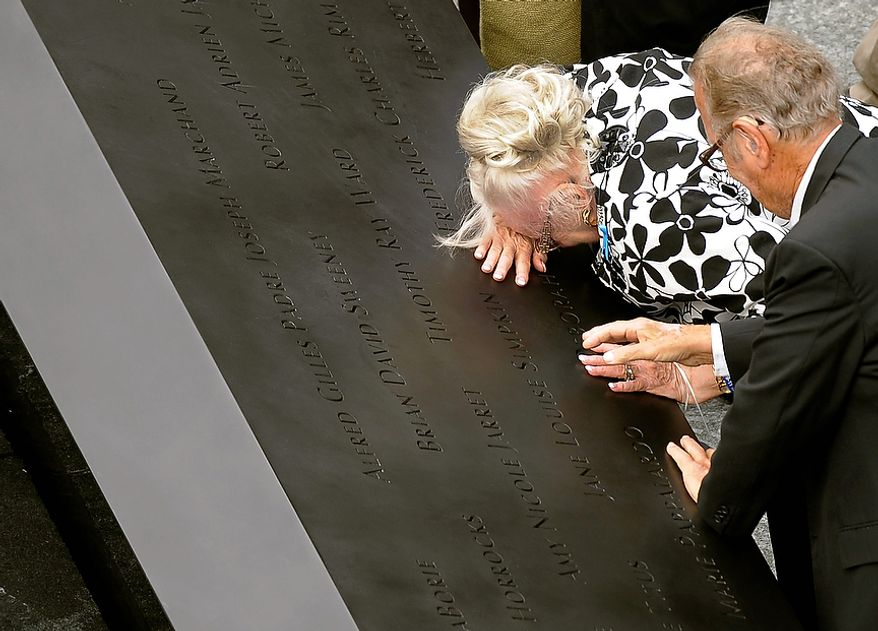 A woman cries over a name on the edge of the south pool at the National September 11 Memorial in New York during the ceremony marking the 10th anniversary of the attacks on the World Trade Center in New York, Sunday, Sept. 11, 2011. (AP Photo/Timothy A. Clary, Pool)