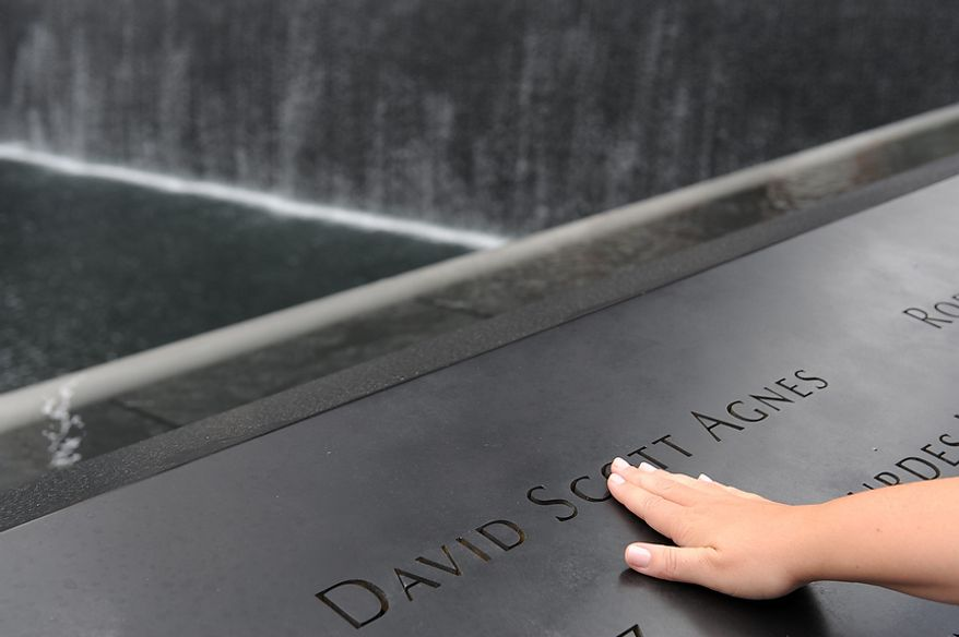 A woman runs her hand over one of the names inscribed on the wall by the north pool of the Sept. 11 memorial, Sunday, Sept. 11, 2011 in New York, as the public gathered to commemorate the 10th anniversary of the terrorist attacks at the World Trade Center. (AP Photo/David Handschuh, Pool)