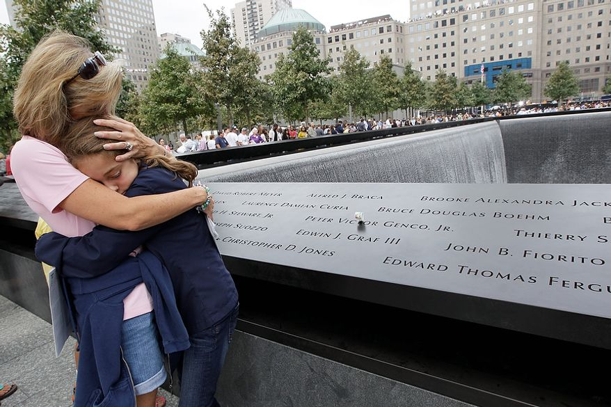 Celeste Pocher embraces her daughter after finding her brother in law's name, John Pocher at the north pool at the National September 11 Memorial during a ceremony marking the 10th anniversary of the attacks at the World Trade Center, Sunday, Sept. 11, 2011 in New York.  (AP Photo/Mary Altaffer)