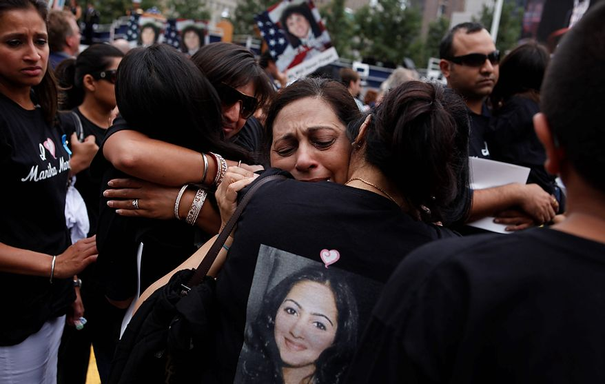 Madhu Narula, of Kings Park, N.Y., reacts after hearing the name of her daughter, Manika Narula, pictured on shirt below, as the names of the victims of 9/11 are read during a ceremony marking the 10th anniversary of the attacks at the National September 11 Memorial at the World Trade Center site, Sunday, Sept. 11, 2011, in New York. (AP Photo/Jason DeCrow)