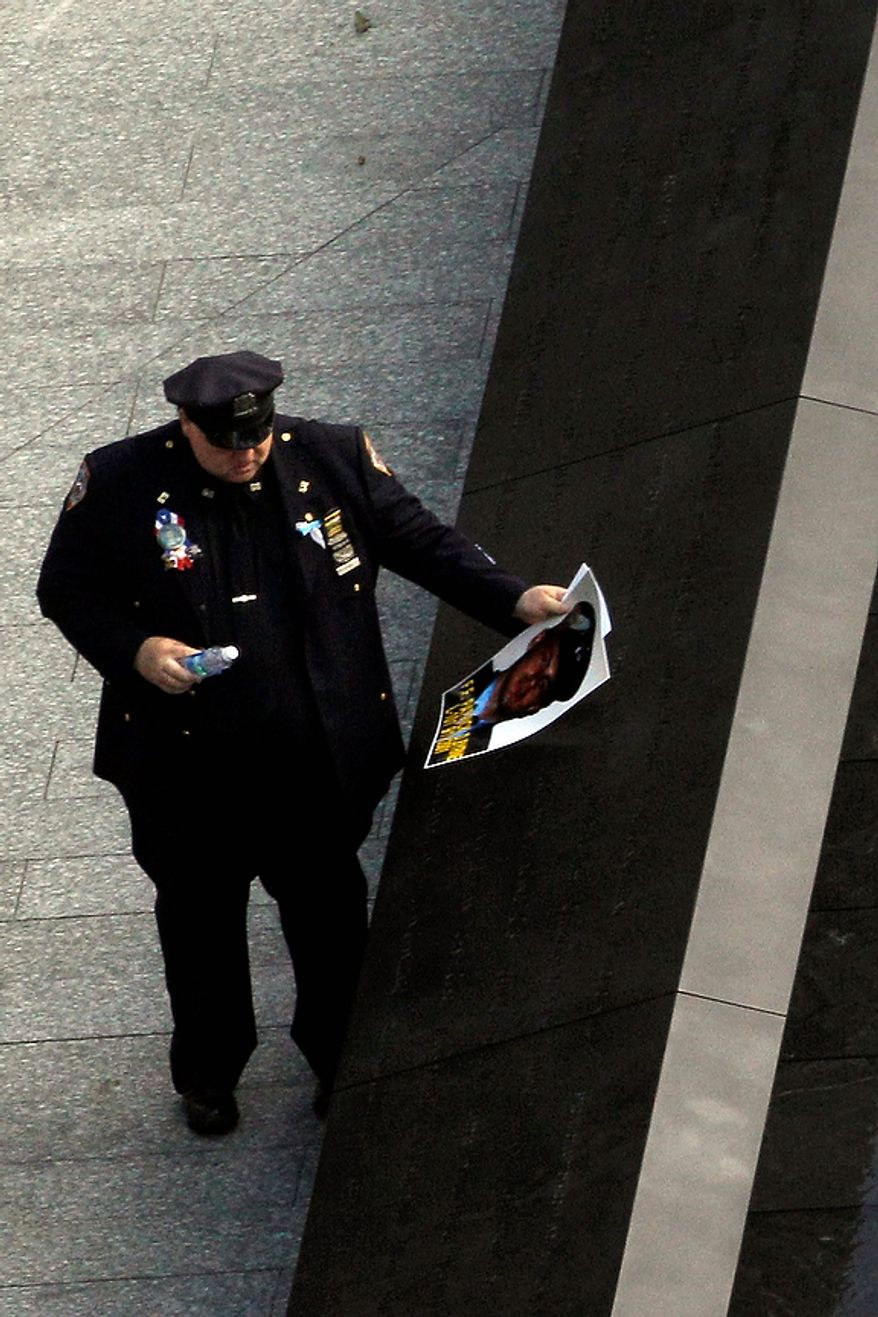 A police officer pays his respects at a waterfall pool during a ceremony marking the 10th anniversary of the 9/11 attacks, at the National September 11 Memorial at the World Trade Center site Sunday, Sept. 11, 2011, in New York. (AP Photo/Matt Rourke)