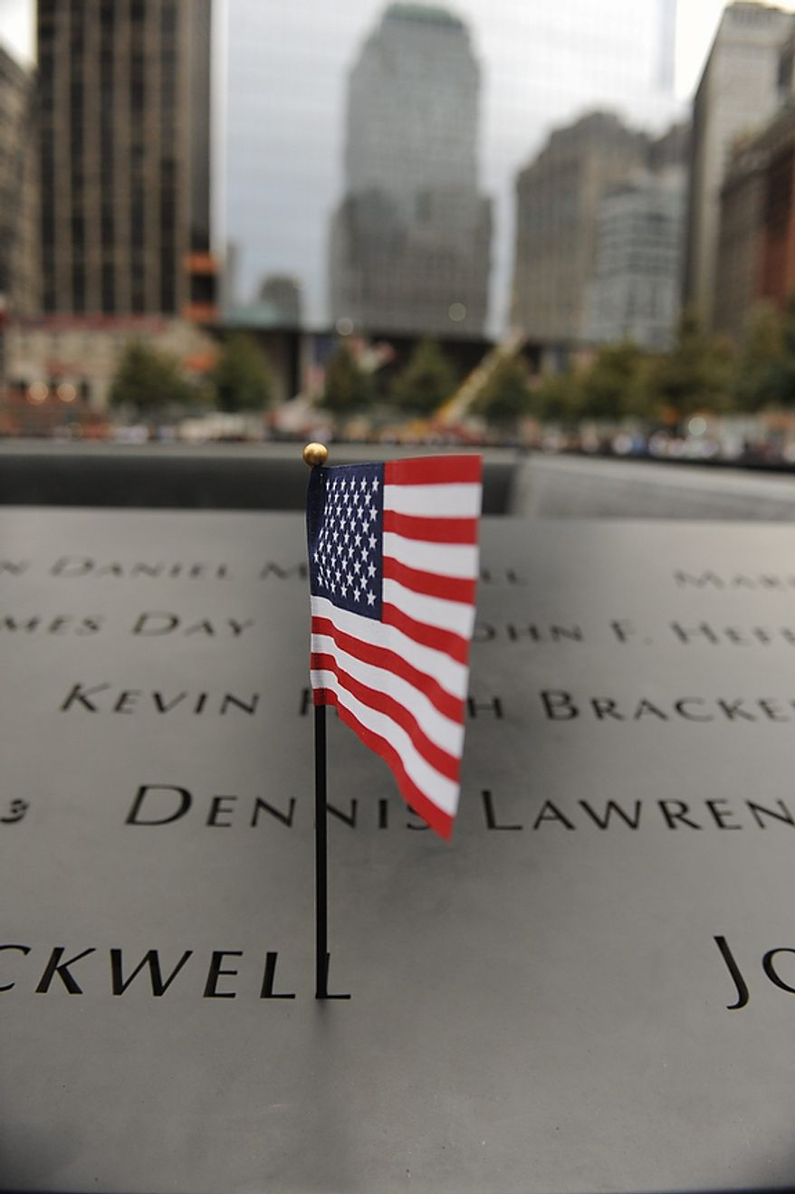 An American flag adorns the edge of the south pool of the Sept. 11 memorial in the World Trade Center site in New York Sunday, Sept. 11, 2011, on the 10th anniversary of the terrorist attacks on the trade center. (AP Photo/Aaron Showalter, Pool)