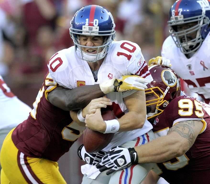 New York Giants quarterback Eli Manning is sacked by Washington Redskins linebacker London Fletcher and nose tackle Chris Neild during the second half Sunday, Sept. 11, 2011, in Landover, Md. (AP Photo/Susan Walsh)