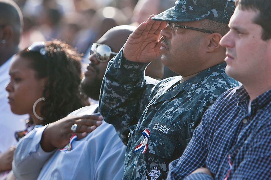 """Raymond Lightbourn (second from right) of Upper Marlboro, Md., salutes during the national anthem at the commemoration of the Sept. 11 attack on the Pentagon, held at the Pentagon Memorial in Arlington on Sunday, Sept. 11, 2011. Mr. Lightbourn, who attended with his nephew John Allen (second from left) of Clinton, Va., lost his sister Samantha Lightbourn-Allen, Mr. Allen's mother, in the attack on the Pentagon. Reflecting on the past 10 years, Mr. Lightbourn said that """"every year opens up the wounds; we relive the experience every time we come here."""" (T.J. Kirkpatrick/The Washington Times)"""