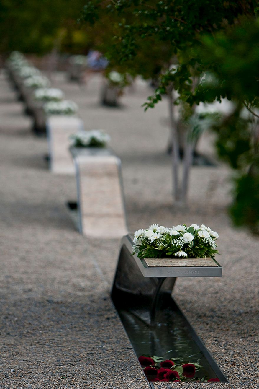 Wreaths laid by a service member during the commemoration of the Sept. 11, 2001, attack on the Pentagon sit on each of the 184 memorial benches of the Pentagon Memorial in Arlington on Sunday, Sept. 11, 2011. (T.J. Kirkpatrick/The Washington Times)