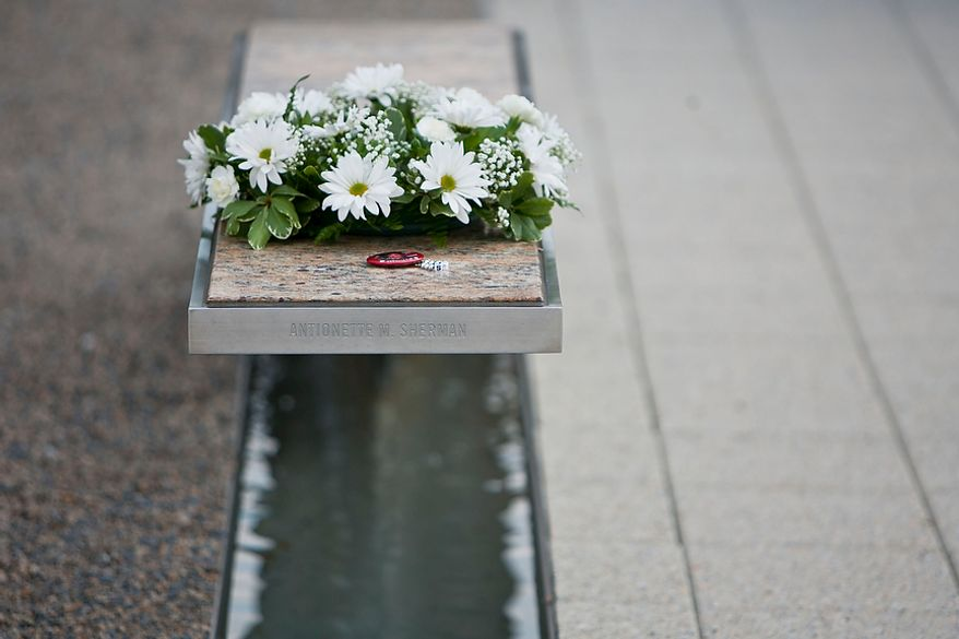 Wreaths laid by a service member during the commemoration of the Sept. 11, 2001, attack on the Pentagon sit on each of the 184 memorial benches of the Pentagon Memorial in Arlington on Sunday, Sept. 11, 2011.