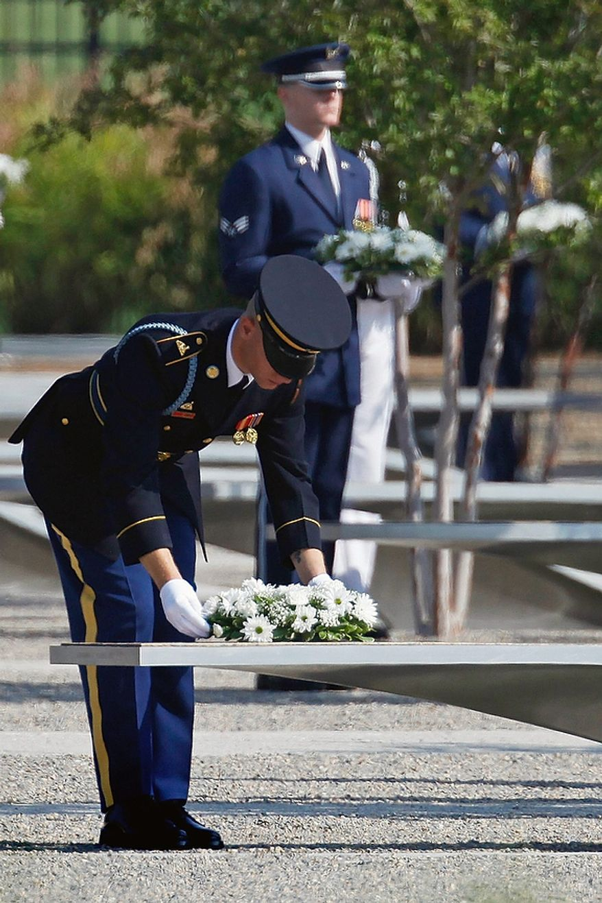Soldiers lay wreaths at the Pentagon Memorial on the benches bearing the names of the victims during the 10th-anniversary ceremony of the Sept. 11 attacks at the Pentagon outside Washington on Sunday, Sept. 11, 2011. (AP Photo/Charles Dharapak)