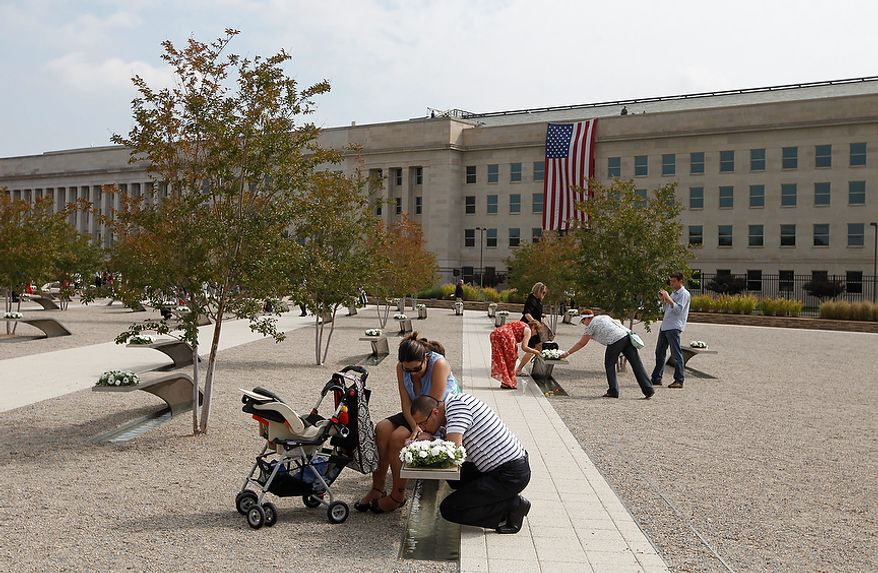 Chin Sok Wells of McKinney, Texas, kisses his 10-week-old baby, Cristian, on his wife, Cathy's lap as they gather around the memorial bench of his sister, Army Spc. Chin Sun Pak Wells, who was killed in the Pentagon attacks, as the 10th anniversary of the Sept. 11 attacks are observed at the Pentagon outside Washington on Sunday, Sept. 11, 2011. (AP Photo/Charles Dharapak)