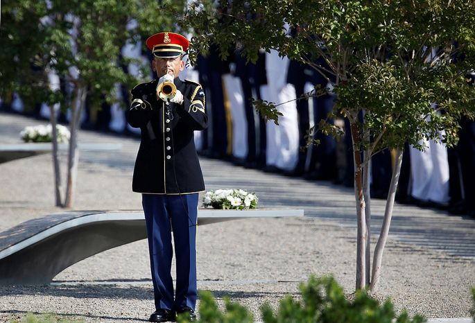 An honor guard bugler plays taps at the the Pentagon Memorial as the 10th anniversary of the Sept. 11 attacks is observed at the Pentagon outside Washington on Sunday, Sept. 11, 2011. (AP Photo/Charles Dharapak)