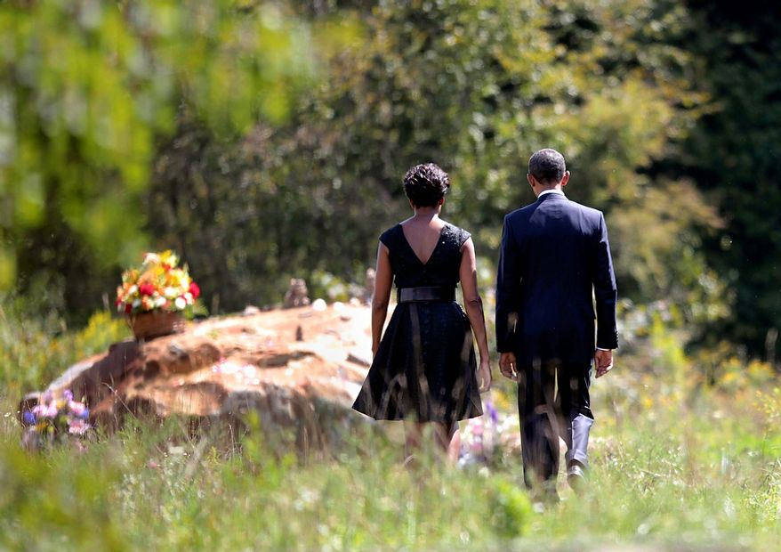 President Barack Obama and first lady Michelle Obama walk to the crash site of Flight 93 during their visit to the Flight 93 National Memorial Sunday, Sept., 11, 2011, in Shanksville, Pa., on the 10th anniversary of Sept. 11. (AP Photo/Pablo Martinez Monsivais)