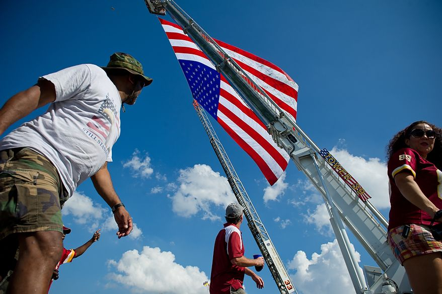 Fans walk by a flag flown from area fire trucks near the stadium before the Washington Redskins play the New York Giants at FedEx Field in Landover, Md. Sunday, September 11, 2011. (Rod Lamkey Jr. / The Washington Times)