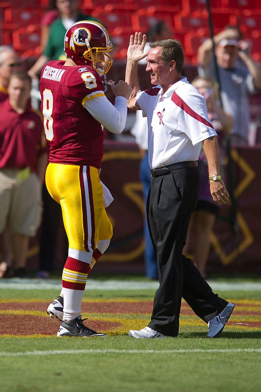 Washington Redskins head coach Mike Shanahan (right) slaps hands with Redskins QB Rex Grossman (8) left before taking on the New York Giants at FedEx Field in Landover, Md. Sunday, September 11, 2011. (Andrew Harnik / The Washington Times)