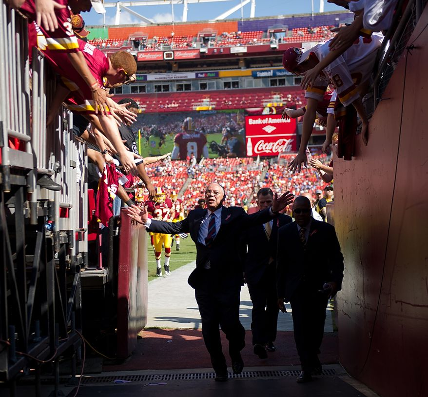 Former Secretary of State Colin Powell is congratulated by Redskins fans as he walks off the field during pre-game as the Washington Redskins ready to play the New York Giants during the 1st quarter at FedEx Field in Landover, Md. Sunday, September 11, 2011. (Andrew Harnik / The Washington Times)