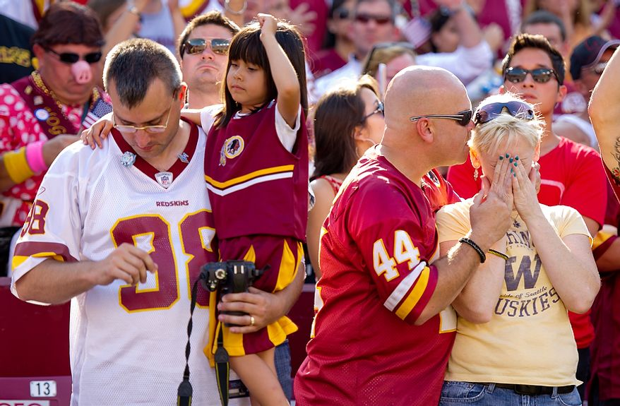 John Brubaker, his daughter Hilary (6), Scott Ryan and his girlfriend Amy Rider (left to right) react to the 9/11 tribute before the Washington Redskins play the New York Giants at FedEx Field in Landover, Md. Sunday, September 11, 2011. (Andrew Harnik / The Washington Times)