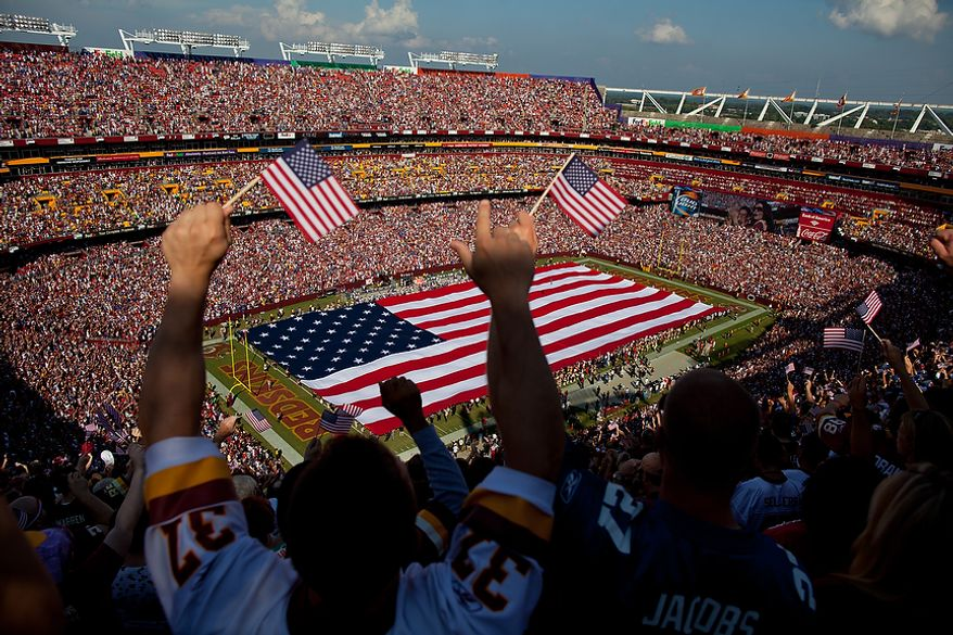 An American flag is unfurled across the field before the Washington Redskins take on the New York Giants on the 10th Anniversary of the attacks of September 11th at FedEx Field in Landover, Md. Sunday, September 11, 2011. (Pratik Shah / The Washington Times)