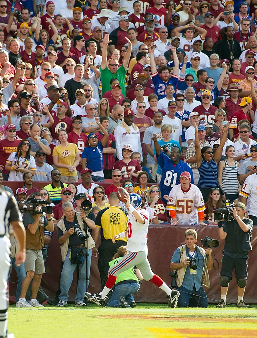 The Washington Redskins can't stop New York Giants QB Eli Manning (10) from picking up the game's first touchdown during the 1st quarter at FedEx Field in Landover, Md. Sunday, September 11, 2011. (Rod Lamkey Jr. / The Washington Times)