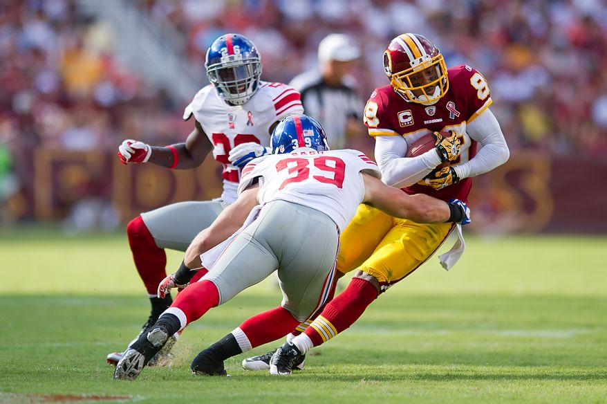 Washington Redskins WR Santana Moss (89) gains 10 yards before being pulled down by New York Giants S Tyler Sash (39) during the 2nd quarter at FedEx Field in Landover, Md. Sunday, September 11, 2011. (Andrew Harnik / The Washington Times)