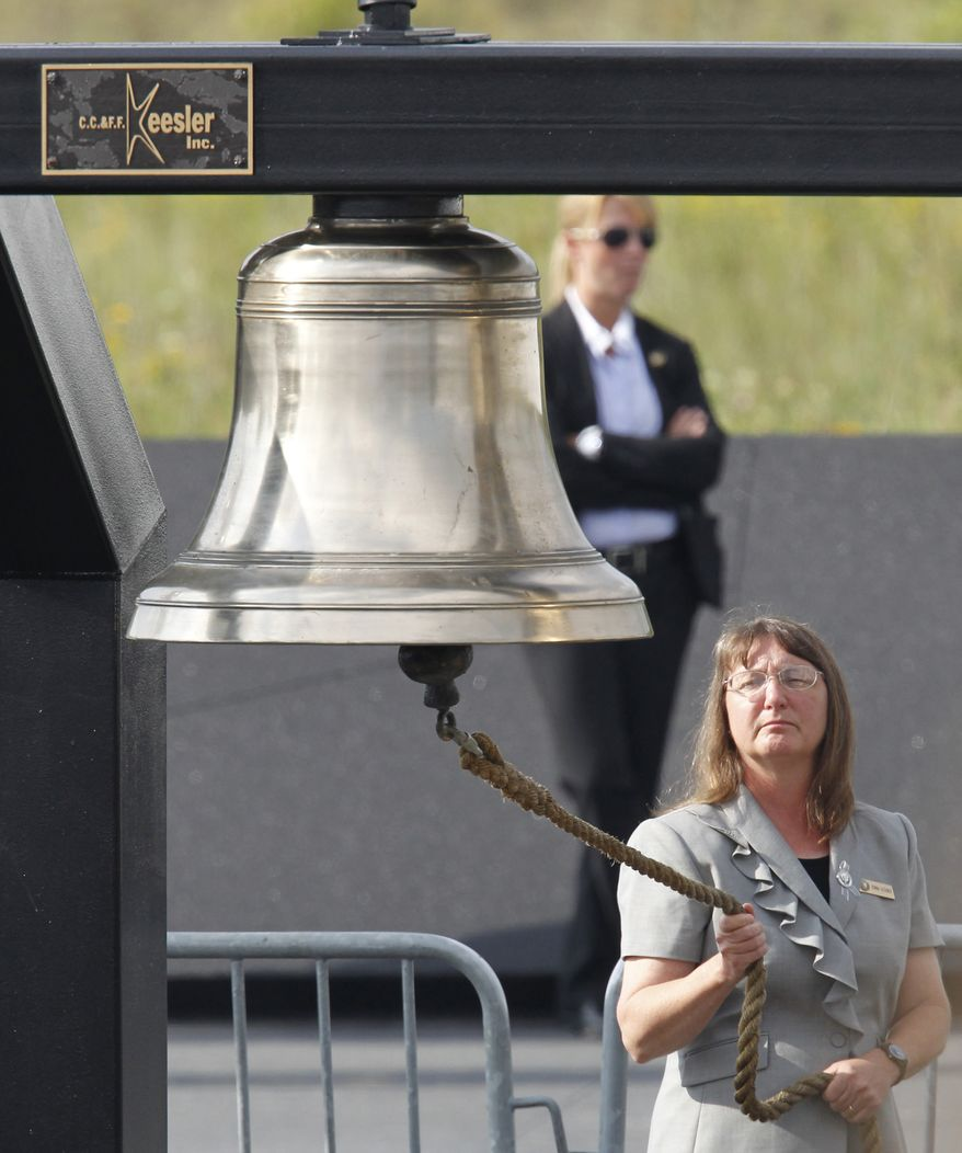 A bell is rung during the reading of the names of passengers and crew who died aboard Flight 93 on Sept. 11, 2001. Memorial services were held near the crash site in Shanksville, Pa., on Sunday, Sept. 11, 2011. (AP Photo/Gene J. Puskar)