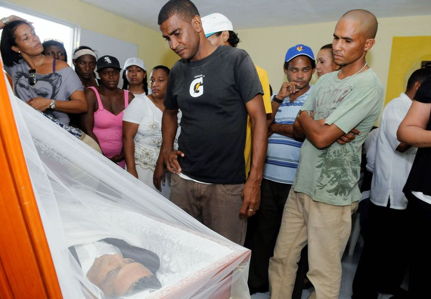 Friends and relatives of journalist Jose Agustin Silvestre attend his funeral in La Romana, Dominican Republic. Silvestre promised to reveal a bombshell in the next edition of his magazine, a story of drugs and corruption involving local businessmen, but he was kidnapped and killed on Aug. 2 before he could do so. (Associated Press)