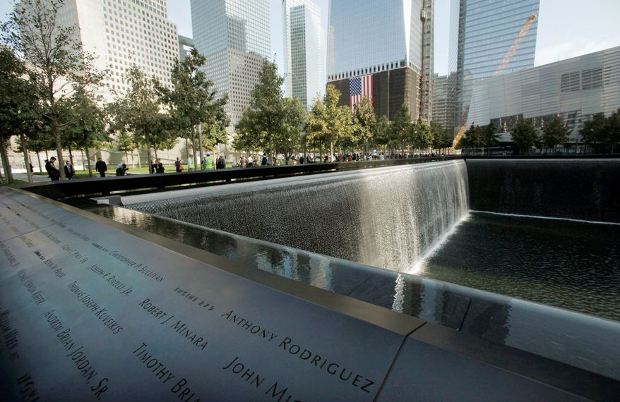 Visitors stroll the grounds near one of the pools at the 9/11 memorial plaza on the World Trade Center site in New York on Monday, the first day the memorial was opened to the public and the day after the 10th anniversary. (Associated Press)