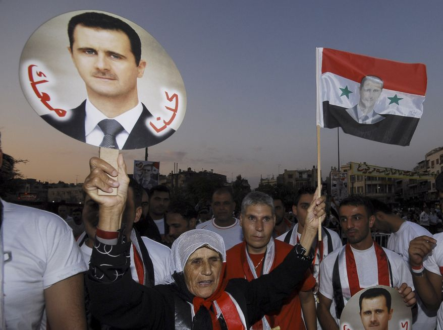 "A pro-Syrian regime supporter shouts slogans while holding a portrait of Syrian President Bashar Assad with Arabic words that read ""We all with you,"" during a rally on Sept. 11, 2011, in Damascus, Syria, to show support for Assad. (Associated Press)"