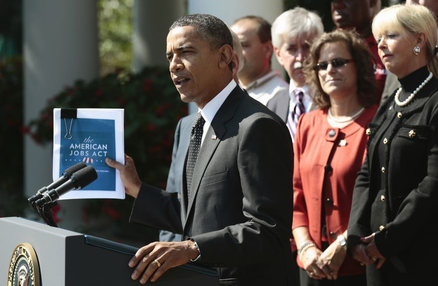 President Obama holds up his proposed American Jobs Act legislation while making a statement at the White House on Sept., 12, 2011. (Associated Press)