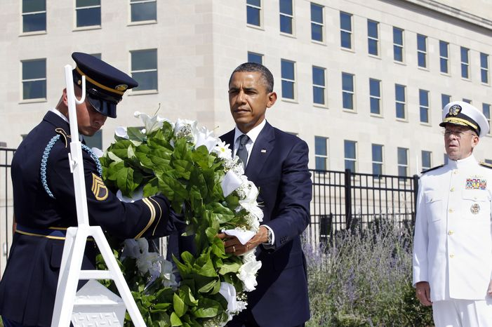 President Obama lays a wreath as the 10th anniversary of the Sept. 11 attacks are observed at the Pentagon in Arlington on Sunday, Sept. 11, 2011. At right is Adm. Mike Mullen, chairman of the Joint Chiefs of Staff. (AP Photo/Charles Dharapak)