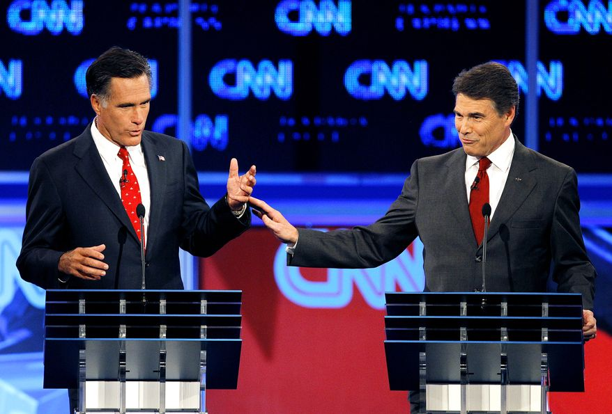 Republican presidential candidates former Massachusetts Gov. Mitt Romney, left, and Texas Gov. Rick Perry gesture during a Republican debate Monday, Sept. 12, 2011, in Tampa, Fla. (AP Photo/Mike Carlson)