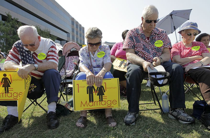 Praying behind the Legislative Building in Raleigh, N.C., on Monday, Sept. 12, 2011, in support of a state constitutional amendment to ban same-sex marriage are (from left) Herbert Rosser and wife Carol of Wake County, N.C., and John Markham and wife Elizabeth of Raleigh. (AP Photo/Ted Richardson)