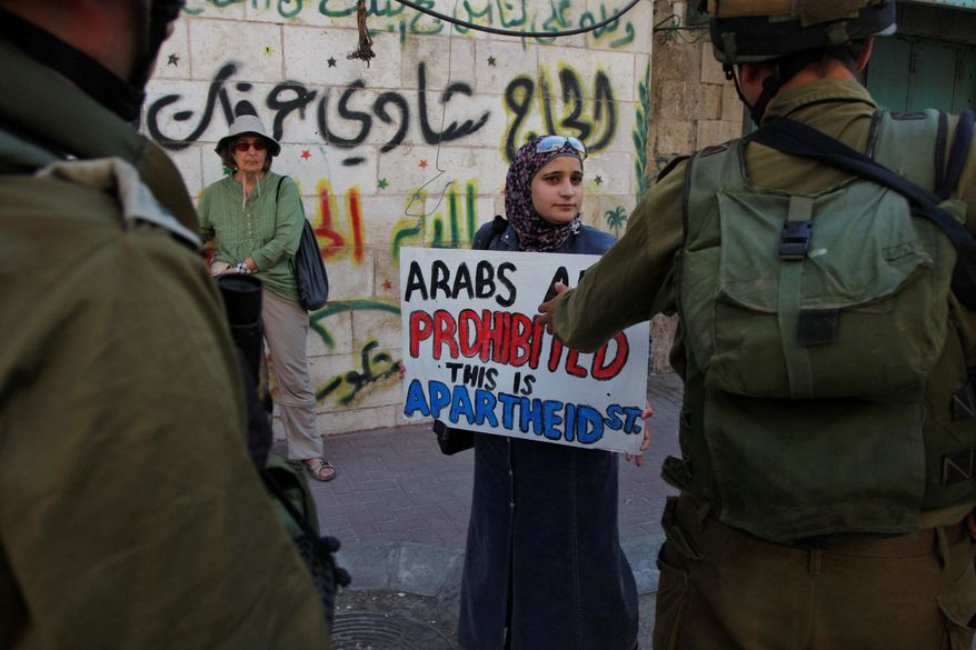 "Israeli soldiers face Palestinian activists during a demonstration Wednesday against the closure of Al-Shuhada Street in the West Bank city of Hebron. Protesters had symbolically renamed the street ""Apartheid Street."" (Associated Press)"