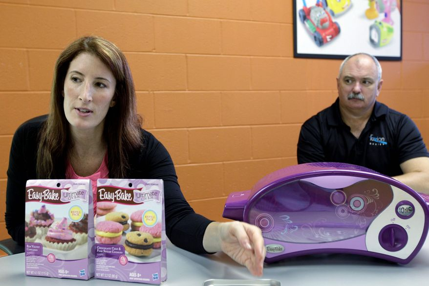 Michelle Paolino, vice president of strategy and marketing for Hasbro, explains the differences in the new version of the Easy-Bake Oven. Listening is Wayne Blatchley vice president of Fuzion Design, which worked on the redesign. (Associated Press)