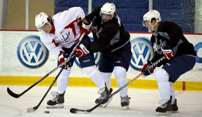 Danick Paquette (left) is defended by Brett Flemming (center) and Samuel Carrier (right) during the Washington Capitals' 2011 Rookie Camp at Kettler Capitals Iceplex in Arlington, Va. on Monday, Sept. 12, 2011. (Rod Lamkey Jr/The Washington Times)