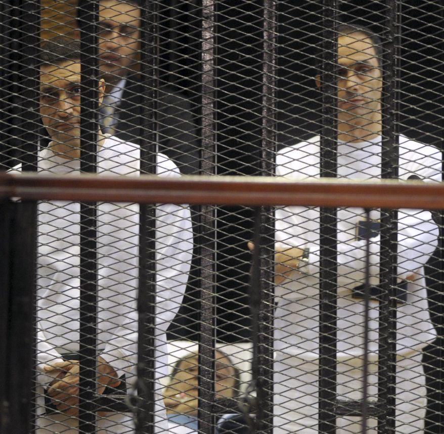 **FILE** Former Egyptian President Hosni Mubarak (center) and his sons, Alaa (left) and Gamal, are seen behind bars during a Aug. 15, 2011, court hearing in Cairo. (Associated Press)