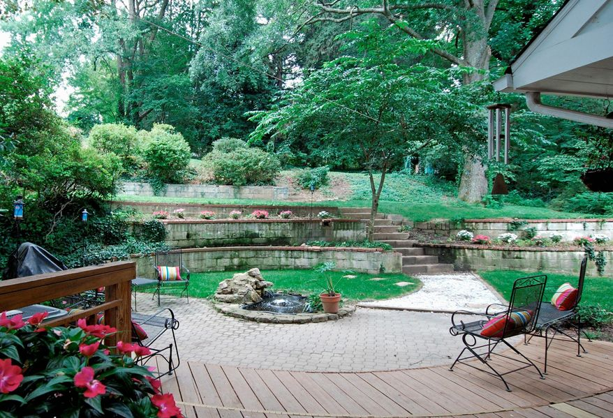 The home's private backyard has multiple terraces, a curving paving-stone patio and a fountain.