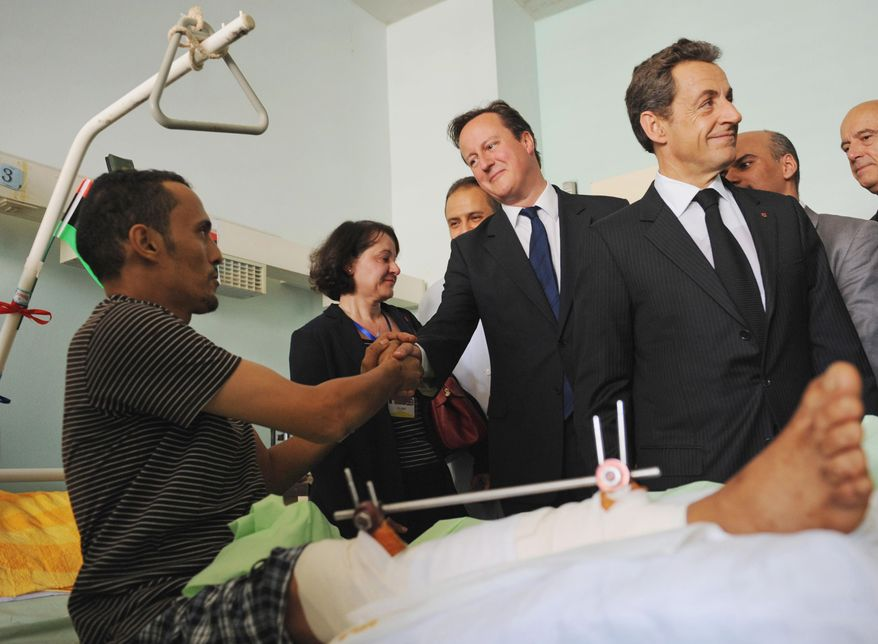 British Prime Minister David Cameron (center) and French President Nicolas Sarkozy (right) meet patients at the Tripoli Medical Center in Tripoli, Libya, on Sept. 15, 2011. (Associated Press)