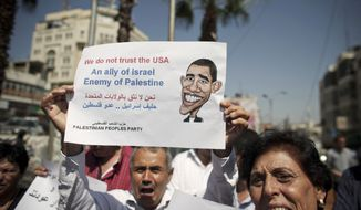 A Palestinian man holds a sign protesting U.S. involvement in the Middle East, in the West Bank city of Ramallah, on Sept. 7, 2011. (Associated Press)