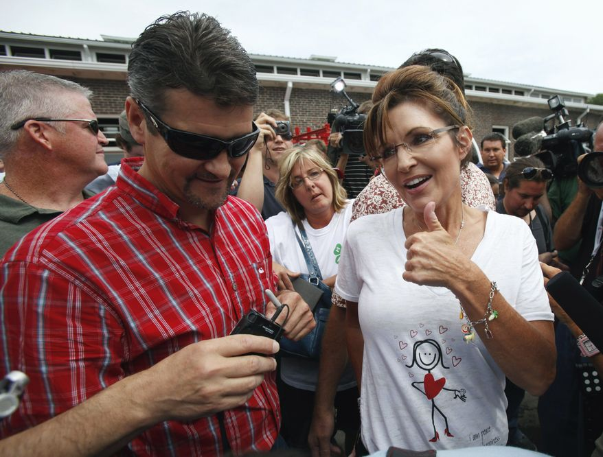 ** FILE ** Former Alaska Gov. Sarah Palin (right) and her husband, Todd (left), greet attendees at the Iowa State Fair in Des Moines, Iowa, on Friday, Aug. 12, 2011. (AP Photo/Charlie Neibergall, File)