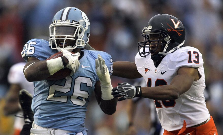 North Carolina's Giovani Bernard runs the ball as Virginia's Chase Minnifield (13) tries to make the tackle during the second half of an NCAA college football game in Chapel Hill, N.C. on Saturday, Sept. 17, 2011. North Carolina won 28-17, and Bernard had 102 yards rushing. (AP Photo/Gerry Broome)