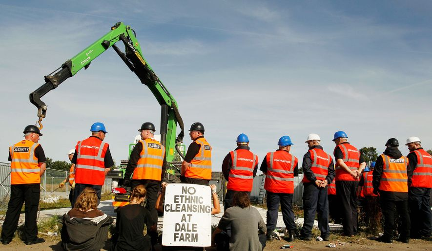 Demonstrators sit and hold a sign of protest as workmen put up fencing at the Dale Farm site occupied by Irish Travelers east of London. On Monday, more than 200 people are to be evicted from the site. (Associated Press)