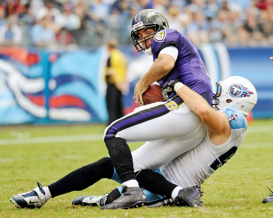 Ravens quarterback Joe Flacco is sacked by Titans defensive tackle Karl Klug for an 8-yard loss in the second quarter. Flacco was sacked three times. (Associated Press)