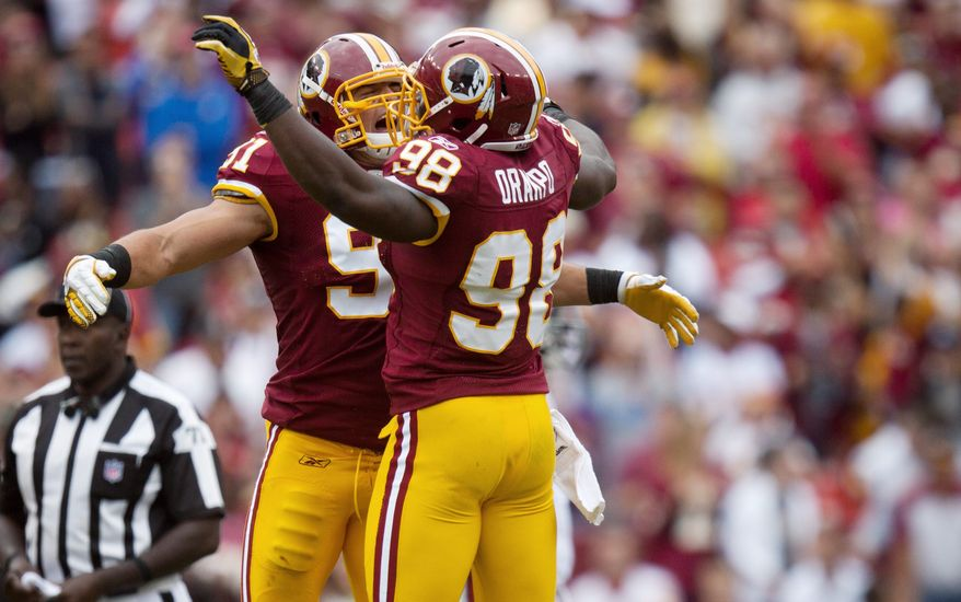 Linebackers Brian Orakpo (98) and Ryan Kerrigan celebrate after the Redskins recovered a fumble during the fourth quarter. Orakpo and Kerrigan pressured Cardinals QB Kevin Kolb much of the afternoon. (Pratik Shah/The Washington Times)