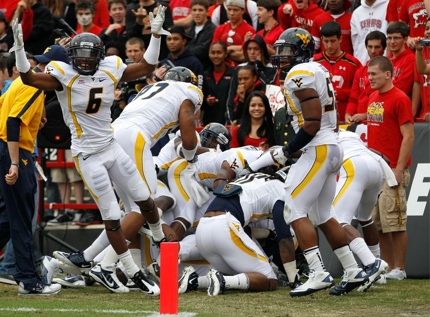 West Virginia players celebrate after defensive back Terence Garvin returned a Danny O'Brien interception for a touchdown in the first quarter of the Mountaineers' 37-31 win Saturday in College Park. O'Brien's three interceptions tied a career-high. (Associated Press)